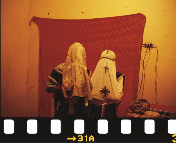 Penitentes de Cabrobó escondem a identidade. O pano de fundo separa os cômodos; do outro lado, os moradores ouvem as ladainhas. Pernambuco, 2006.