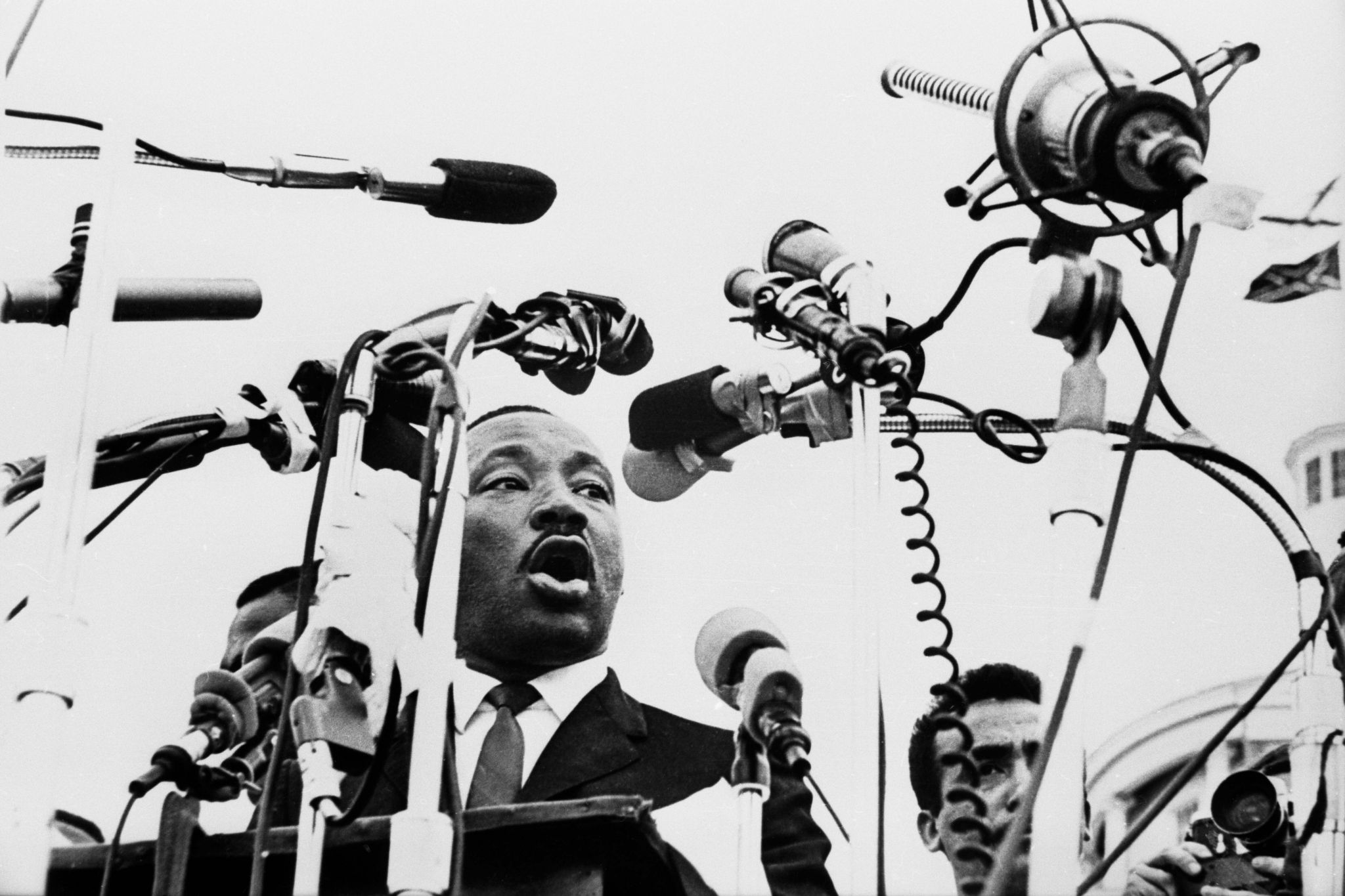 21.)-Dr.-king-speaks-into-a-web-of-microphones-as-he-addresses-25,000-marchers-at-State-Capitol-at-conclusion-of--March.