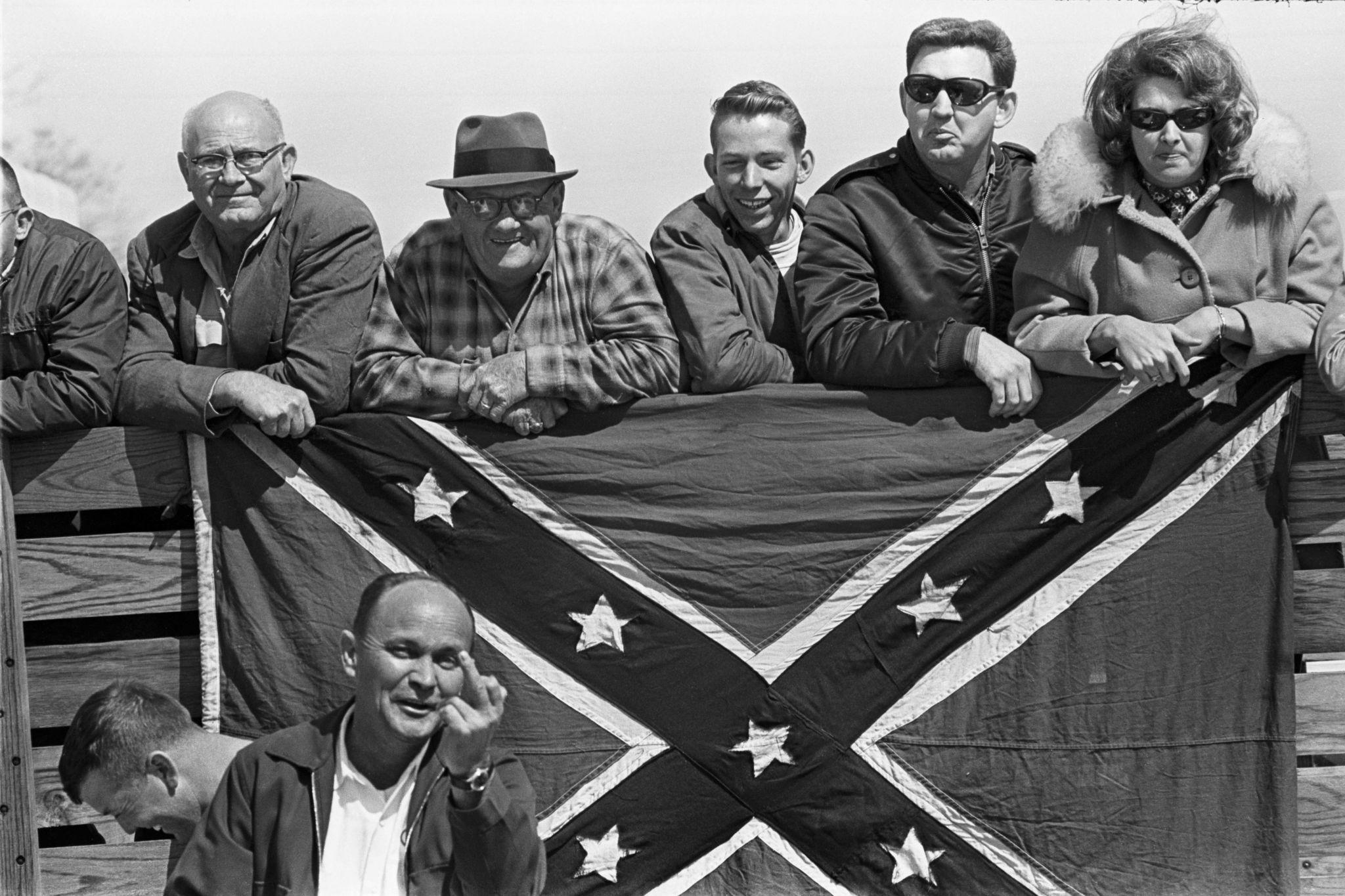 Brancos confrontam os marchantes por detras da bandeira da Confederação, um mostra o dedo