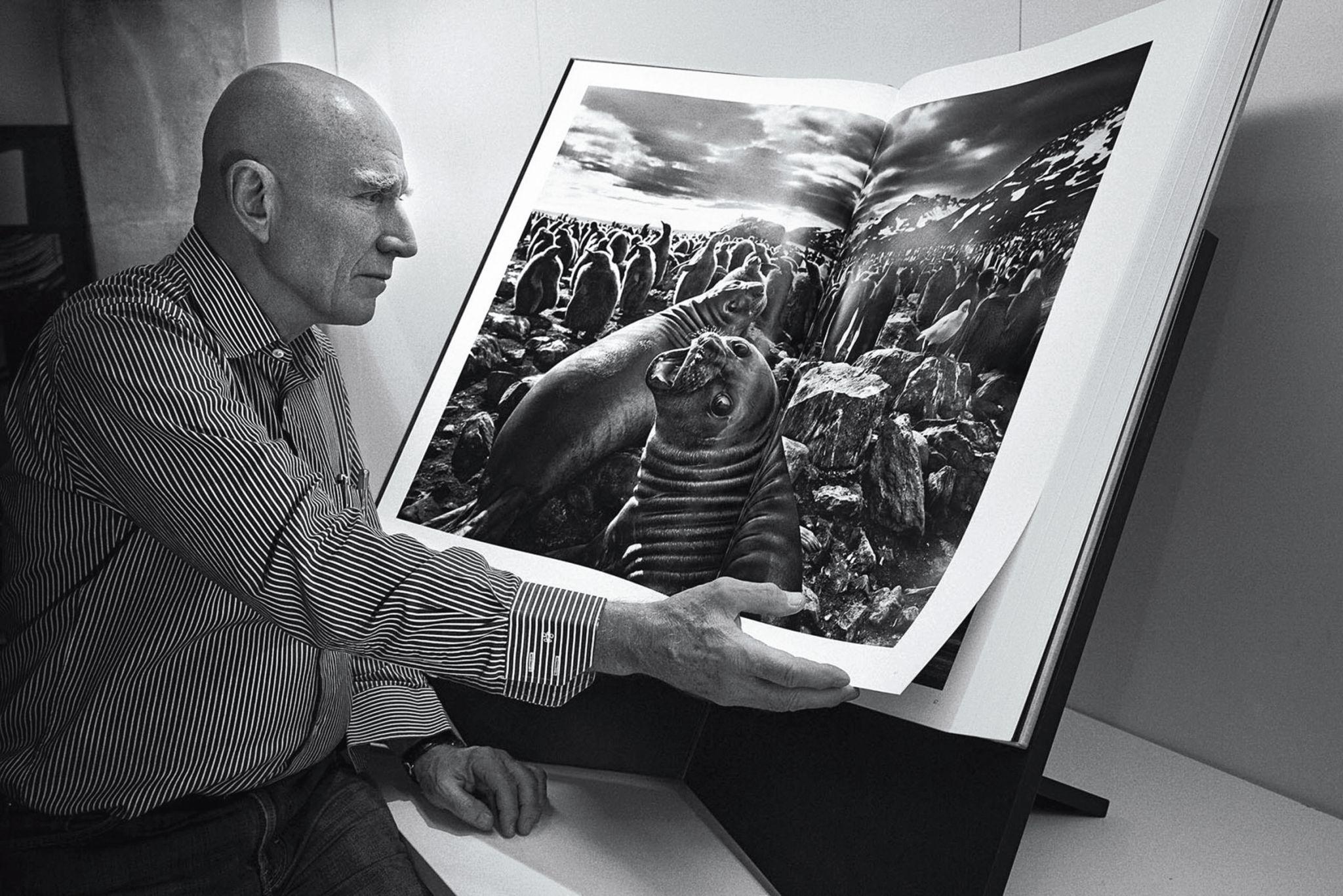 Sebastião Salgado com uma das edições do livro Gênesis, 2013