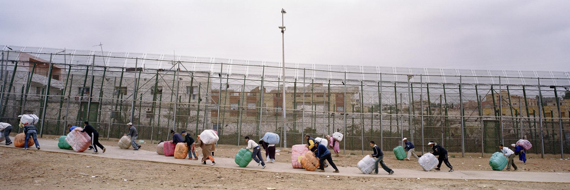 Kai Wiedenhöfer, marroquinos empurrando pacotes de roupas em direção a uma entrada para o Marrocos a partir do enclave de Mellila, Espanha, 2009.