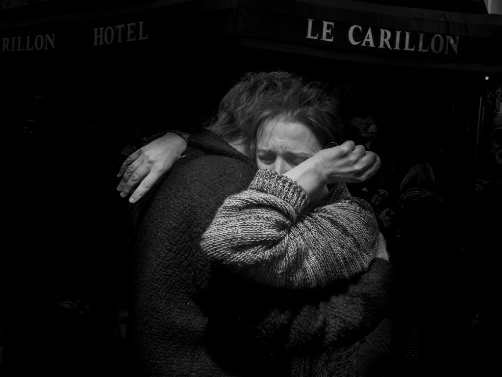 Duas pessoas se abraçam em frente ao bar Le Carillon, um dos locais em que terroristas armados abriram fogo. Paris, 14 de novembro de 2015. © Alex Majoli/Magnum Photos