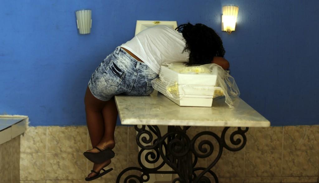 Mãe do menino Ryan Gabriel, morto por bala perdida em Madureira, deitada sobre o caixão do filho no velório no Cemitério de Irajá. Foto de Gabriel de Paiva/ Agência O Globo.