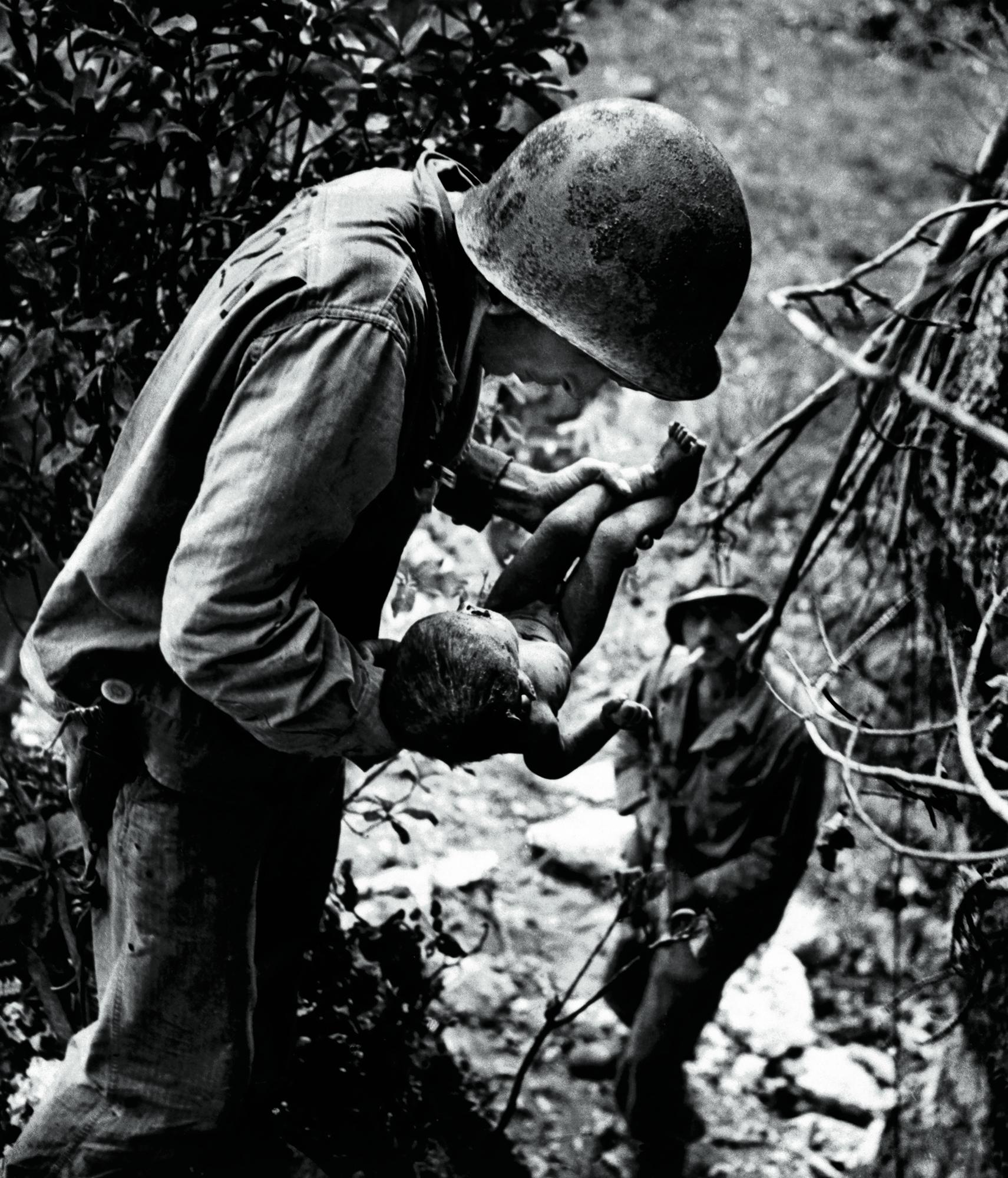 Fuzileiro naval segura criança ferida encontrada nas montanhas. Batalha da ilha de Saipan, Campanha do Pacífico, junho de 1944. ©W. Eugene Smith/Magnum Photos/Latinstock